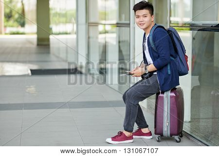 Handsome Vietnamese man sitting on his suitcase when waiting for departure