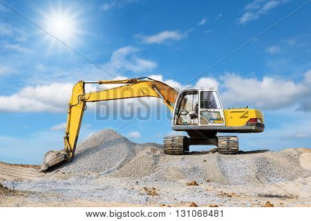 Excavator parked on the mound with sunlight and blue sky background.