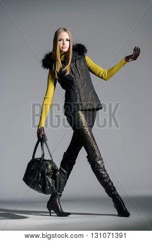 full-length fashion model in autumn/winter clothes holding handbag posing