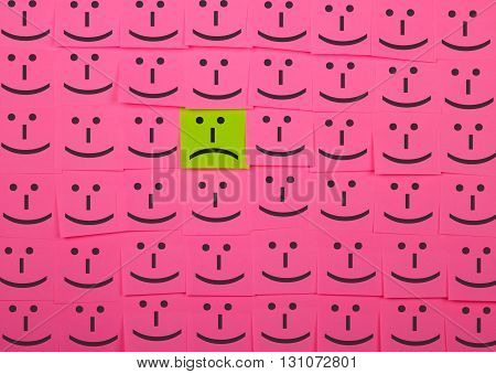Unhappy and happy concept. Background of pink sticky notes. Unhappy sticky note is among happy sticky notes.