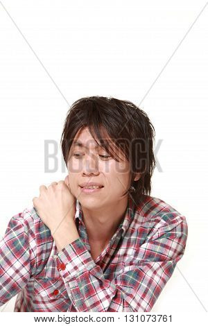 portrait of young Japanese man suffers from neck ache on white background