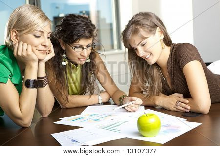 Casual businesswomen leaning on table in meeting room, discussing finacial charts.