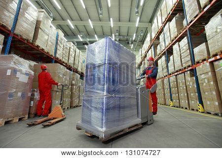 Logistics - two workers in uniforms and safety helmets working in storehouse