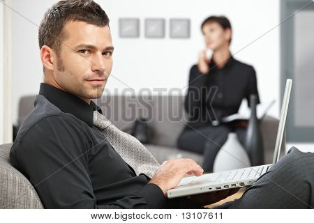 Young businessman sitting at office lobby working with laptop computer.