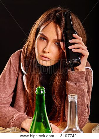 Drunk girl holding bottle of alcohol and looking camera. Soccial issue alcoholism.
