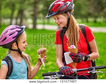 Bikes bicyclist girl. Girls wearing bicycle helmet and gloves with rucksack rides bicycle. Girls biking eating ice cream cone into summer park. Bicyclist is looking at each other.