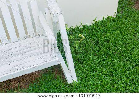 white wooden bench seat in green grass garden