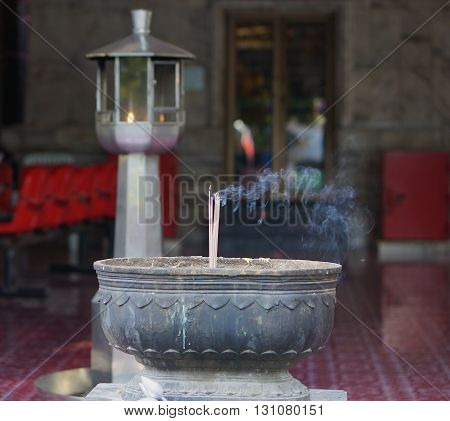 Incense sticks on joss stick pot are burning and smoke use for pay respect to the Buddha.
