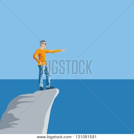Young man stands on the high rock above the sea and points by hand to the far lands