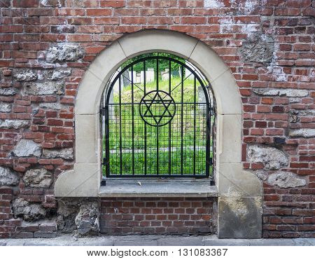 Krakow, Poland - May 21, 2016: The Old historic Jewish Remuh Cemetery in Kazimierz district in Krakow Poland established in 1535 viewed through the grille with the Star of David