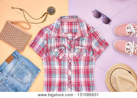 Street style Fashion girl clothes accessories set. Hipster woman, trendy handbag, plaid shirt, denim, gumshoes, hat necklace and sunglasses. Urban creative outfit.Overhead, top view on pink background