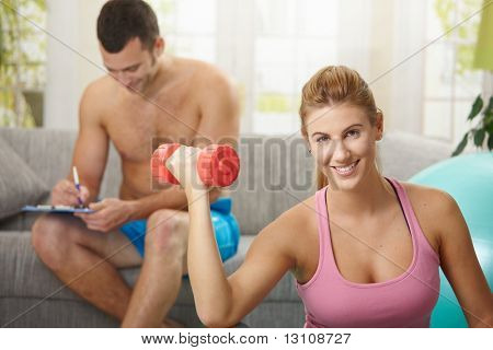 Young woman doing biceps exercise with dumbbell sitting on fittness mat at home, smiling.