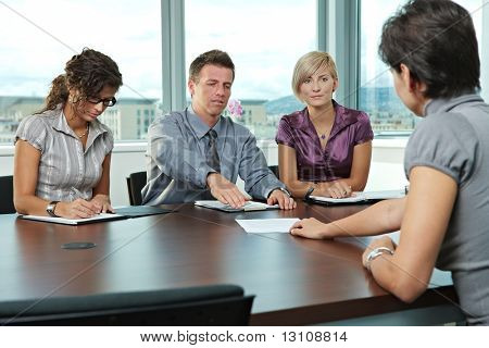 Panel of business people sitting at table in meeting room conducting job interview. Applicant showing documents.