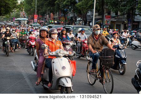 Ho Chi Minh city, Vietnam - April 19, 2015 : crowed scene of city traffic in rush hour, crowd of people wear helmet, transport by motorcycle, stop at red light in stress situation, Vietnam