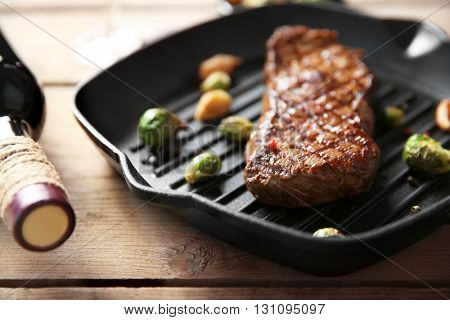 Grilled steak on grill pan with wine on wooden table