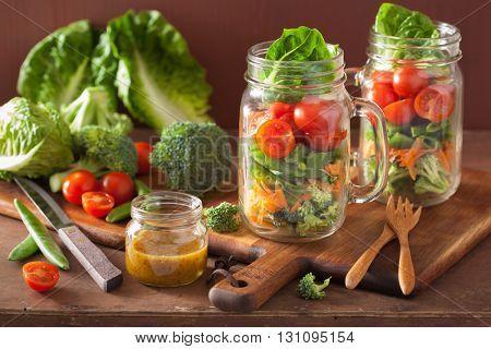 healthy vegetable salad in mason jar. tomato, broccoli, carrot, pea