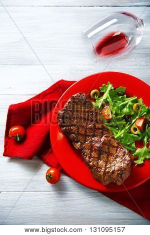 Grilled steak with vegetable salad and wine, closeup
