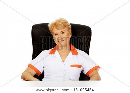 Smile elderly female doctor or nurse sitting behind the desk