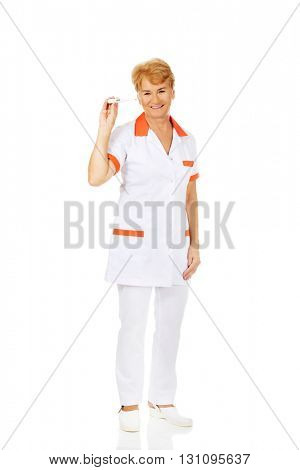 Smile elderly female doctor or nurse holding thermometer