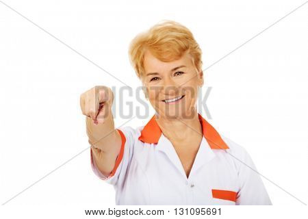 Smile elderly female doctor or nurse pointing at camera