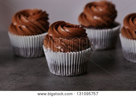 Chocolate cupcakes on grey background, close up