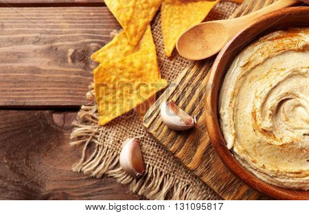 Wooden bowl of tasty hummus with chips on table