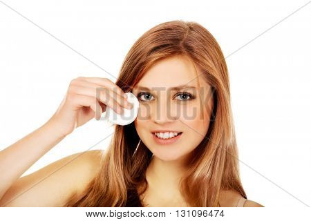 Teen woman removing makeup with cotton pad