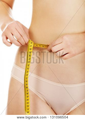 Fit woman measuring her waist with a tape measure