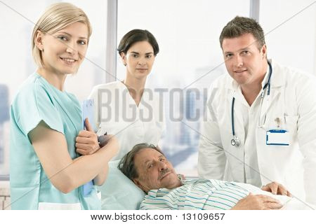 Old male patient lying in hospital bed wearing pyjama, medical team around, smiling at camera.?