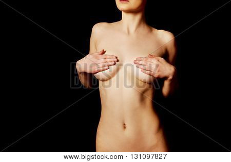 Topless woman covers her tits.