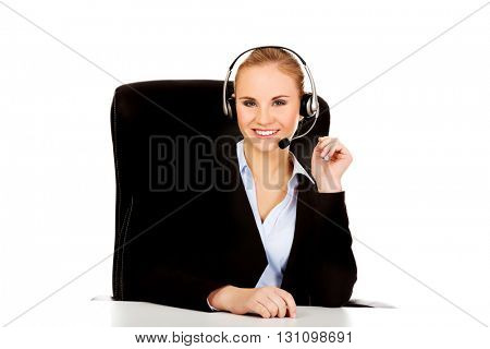 Smiling phone operator in headphones sitting  behind the desk
