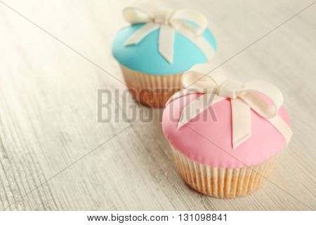 Tasty cupcakes with bow on grey background