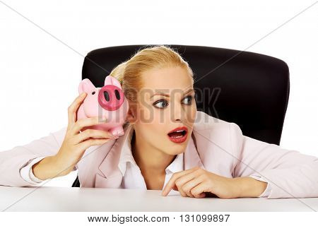 Shocked business woman sitting behind the desk and listen too her piggybank