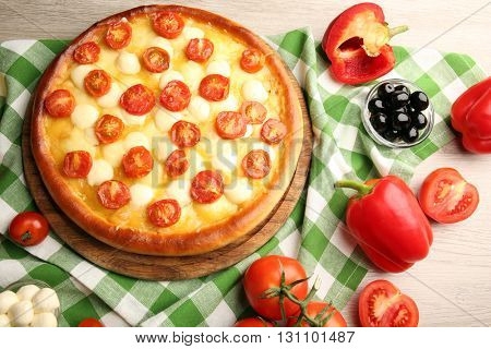 Pizza Margherita with vegetables on green napkin
