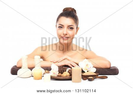 Beautiful young girl with aromatic candles and salt lying on brown towel, isolated on white