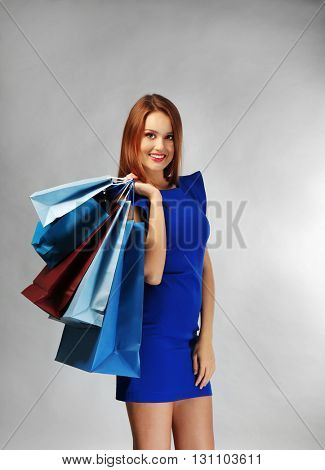 Young pretty woman with shopping packages on gray background