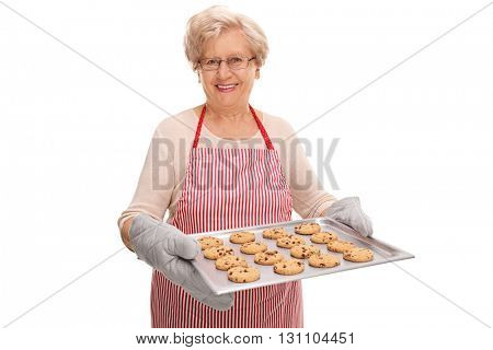 Cheerful mature lady holding a tray full of homemade chocolate chip cookies isolated on white background