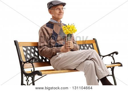 Romantic senior gentleman holding flowers and waiting for his date seated on a wooden bench