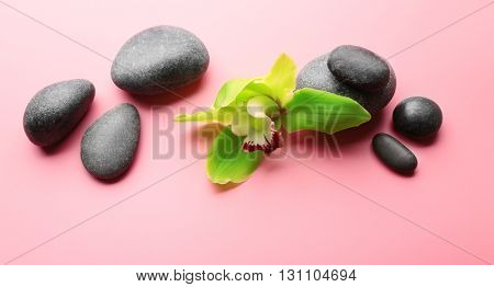 Spa stones and yellow orchid on pink background