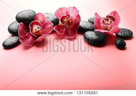 Spa stones and red orchid on pink background