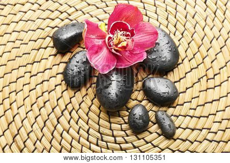Spa stones and red orchid on a wicker mat, closeup