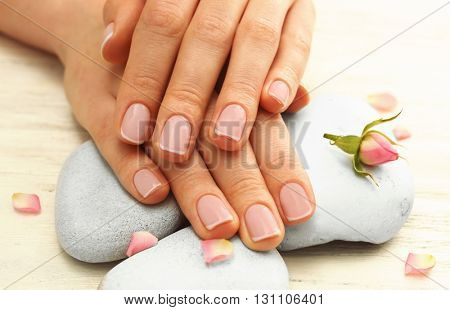 Spa concept. Woman hands with beautiful rose petals on wooden background, close up