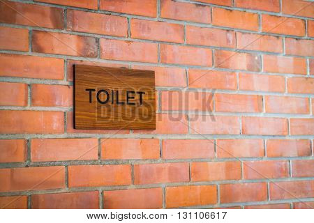 Toilet sign on grunge brick wall background