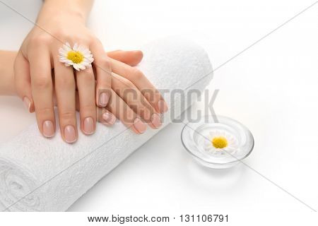 Woman hands with beautiful manicure on white towel, close up