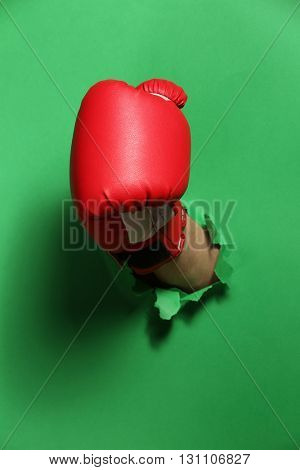 Male hand in boxing glove through green paper
