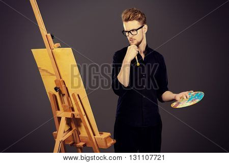 Male artist paints on an easel in the workshop. Occupation.
