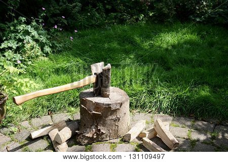 Chopping block with woodcleaver axe in a garden.