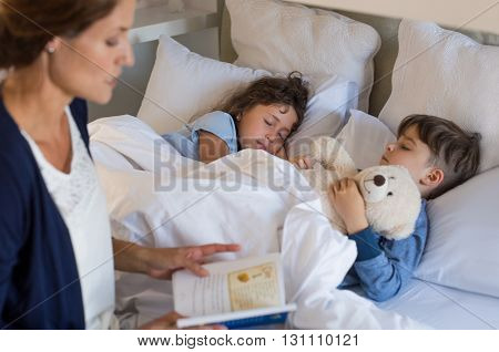Mother reading bed time stories to children. Brother and sister sleeping peacefully. Mother putting son and daughter to sleep.