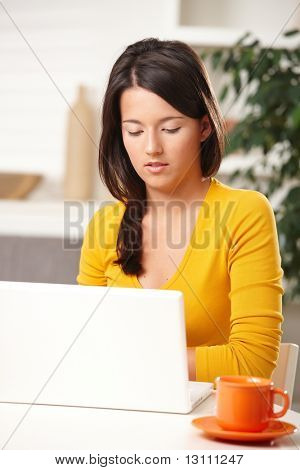 Beautiful teen girl learning with laptop computer sitting at table with mug.