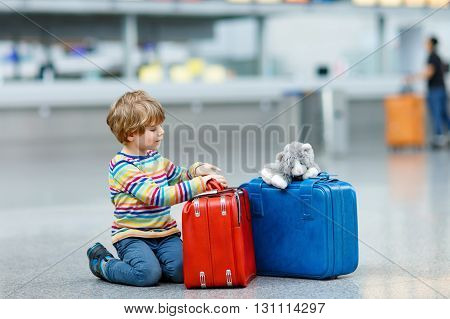 Cute little kid boy with blue and red suitcases and toy on international airport. Happy child wating for flight and going on vacations.